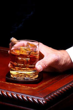 unhealthful: Mans Hand Holding Whiskey Glass and Cigar on wood & Leather Table Top Stock Photo