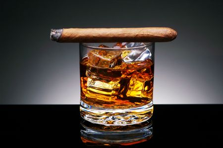 unhealthful: Lit Cigar resting on Glass of Whiskey and Ice cubes Stock Photo