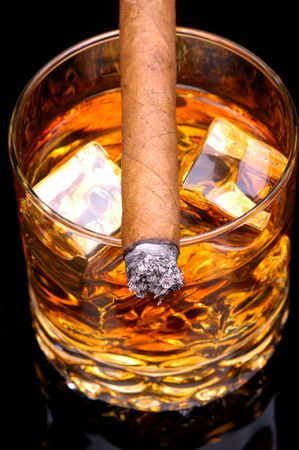 unhealthful: Lit Cigar resting on Glass of Whiskey and Ice cubes - close, vertical