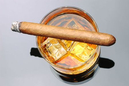 unhealthful: Lit Cigar resting on Glass of Whiskey and Ice cubes over gray reflective background Stock Photo