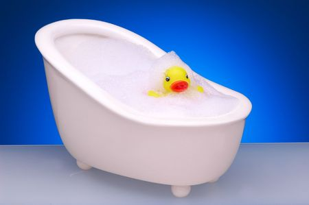 Yellow Rubber Duck in Footed Bathtub with Bubbles photo