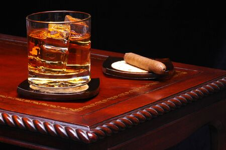 unhealthful: Whiskey in Glass on Table with Cigar and black background
