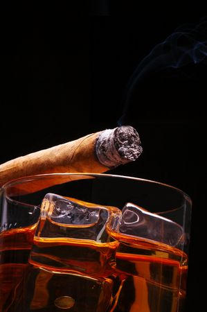 Lit Cigar resting on Glass of Whiskey and Ice cubes with wisp of smoke and black background, low angle
