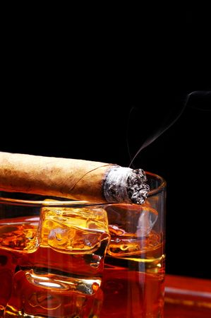 icecube: Lit Cigar resting on Glass of Whiskey and Ice cubes with wisp of smoke and black background