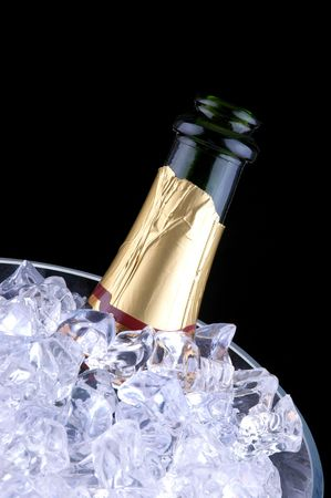 Open Champagne Bottle in Crystal Ice Bucket isolated over black photo