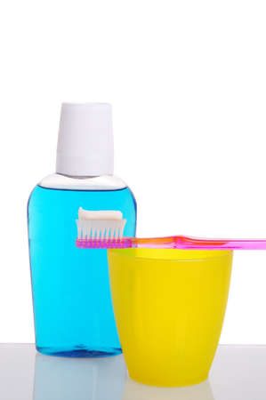 Toothbrush on Cup with Mouthwash Bottle isolated on white