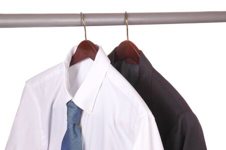 Mens Dress Shirt and Suit on Hanger in closet isolated over white Stock Photo
