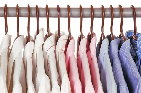 in men's shirt: Mens Dress Shirts on Hangers in closet isolated over white Stock Photo