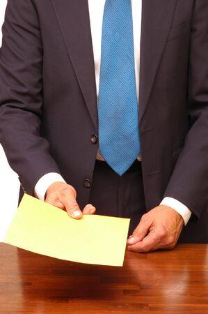 handing: Standing Businessman Handing Large Envelope Across Desk