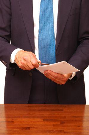 envelope: Standing Businessman Opening an Envelope at Desk Stock Photo