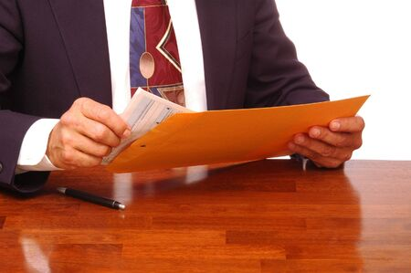 Businessman at Desk Removing Forms from an Envelope isolated over white Stok Fotoğraf