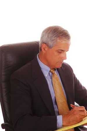legal pad: Mature Businessman Seated in Black Leather Chair with Legal Pad and Pen isolated over White