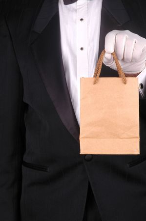 Man in Tuxedo Holding a Small Brown Bag - torso shot Stock Photo - 2995306