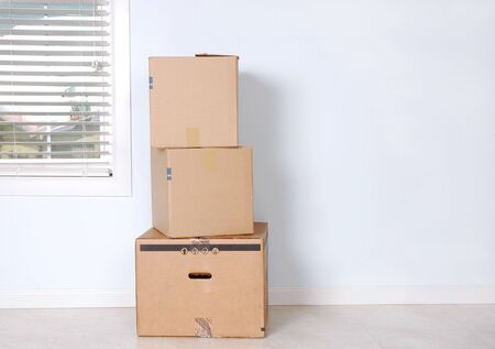Moving Boxes in an Empty Room with Window Stock Photo