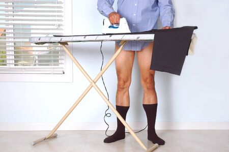 Man in Dress Shirt and Dark Socks and Bare Legs Ironing His Pants in an Empty Room photo