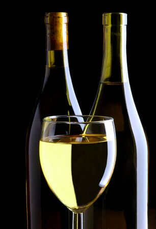 backlights: White Wine Glass and Two Bottles on Black Background Stock Photo