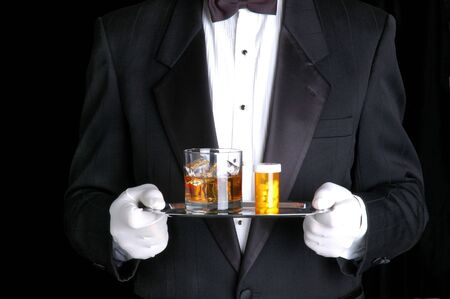 Man Holding Pills and cocktail on Silver Tray photo