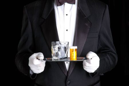 Man Holding Pills and Glass of Water on Silver Tray photo