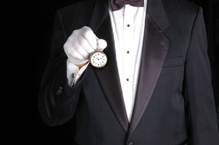 Butler in Tuxedo Holding a Pocket Watch with the Face pointing towards camera Stock Photo