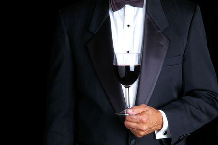 Man in Tuxedo Holding a Glass of Red Wine photo