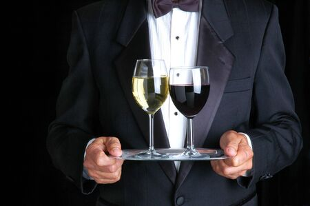 Man Wearing Tuxedo Holding Two Glasses of Wine on a Tray photo