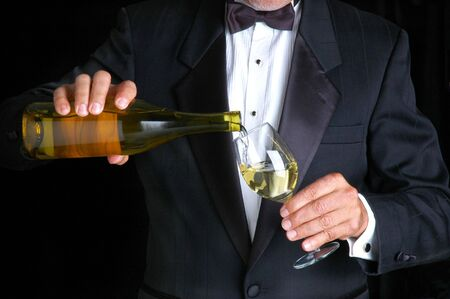 Sommelier in Tuxedo Pouring White Wine from a Bottle into Wine Glass