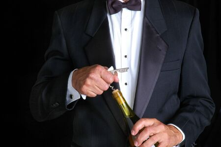 Waiter in Tuxedo Opening a Bottle of Wine Stock Photo
