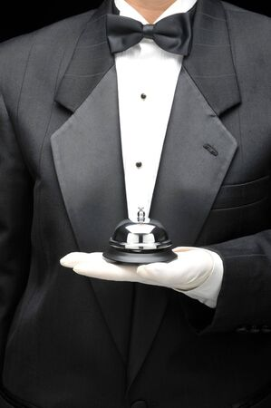 Butlers holding call bell in gloved hand in front of body, torso only Stock Photo - 3659429