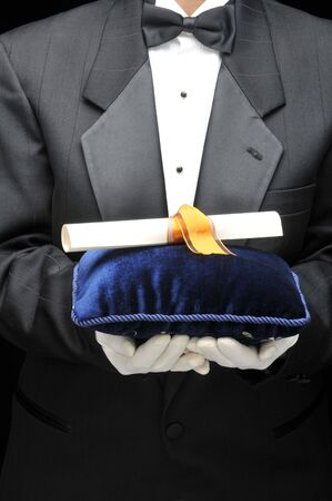 valet: Butler holding a velvet pillow with diploma in front of body - torso only Stock Photo