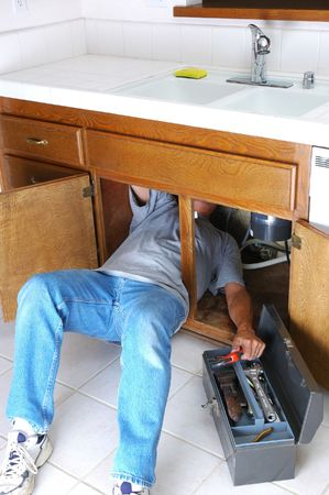 Man with body half under sink cabinet and reaching for wrench in toolbox Stock Photo - 3675745