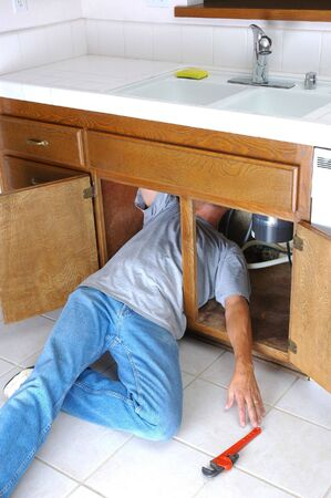 Man Under Kitchen Sink Reaching for Pipe Wrench Stock Photo - 3675737
