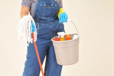 salopette: Femme en combinaison tenue d'un seau plein de fournitures de nettoyage et de ratissage