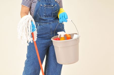 Woman in overalls holding a bucket full of cleaning supplies and mop