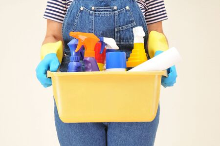 Woman in overalls holding a bucket full of cleaning supplies