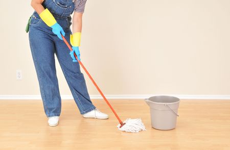 Woman in overalls mopping floor in vacant room