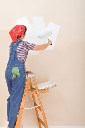 Woman on ladder using roller to paint the interior of her  photo