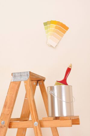 Paint can on shelf of wooden ladder with paint brush and color chips on wall Stok Fotoğraf