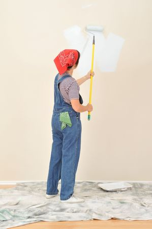 Woman in overalls using roller on extension pole painting wall