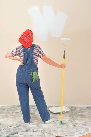 Woman in overalls holding paint roller on extension pole looking a wall