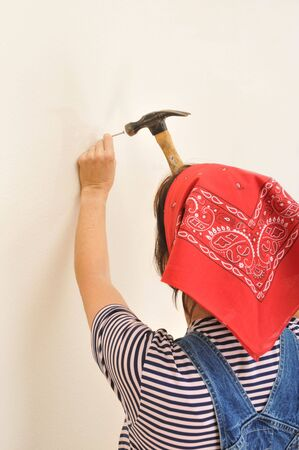 Woman wearing overalls hammering a nail into a wall Stock Photo - 3675749