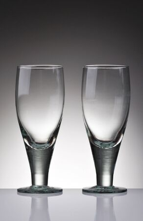 Two empty water goblets on light to dark background with reflections in tabletop