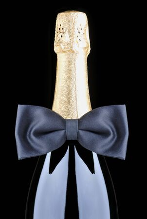 bouteille champagne: Bouteille de champagne avec n?ud papillon noir isol� sur fond noir Banque d'images