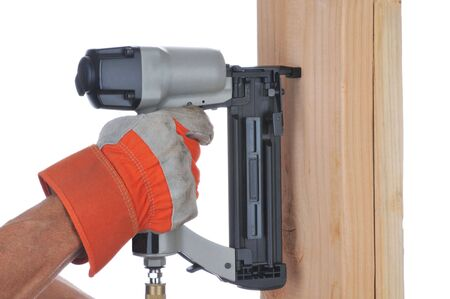 nails: Construction Workers hand with nail gun and boards isolated over white Stock Photo