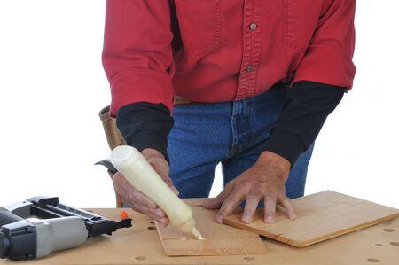 板に接着剤を適用する木工業のクローズ アップ