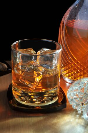 sidelight: Glass of Whiskey with Decanter with strong warm sidelight Stock Photo