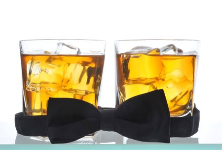 barware: Two Whiskeys and Bow Tie on glass bar table isolated on white