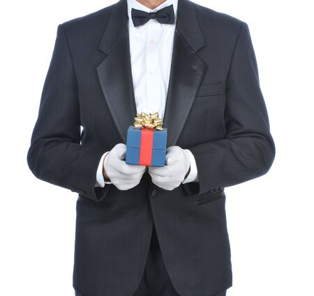 torso only: Man wearing a tuxedo and holding a gift box isolated over white - torso only