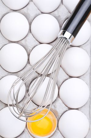 implementing: Whisk on eggs in carton with one broken showing the yolk