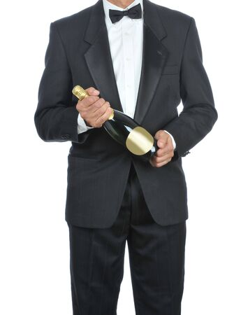 Man wearing a tuxedo and holding a bottle of Champagne isolated over white - torso only Stock Photo - 4174802