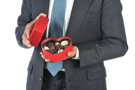 Man in business suit holding a heart shaped box of valentines candy - isolated over white photo